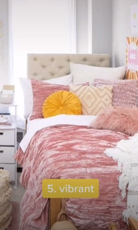 A vibrant-themed bedroom idea with a pink and gold color motif from TikTok user katiefeeneyy.