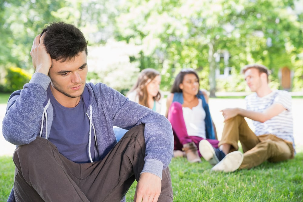 A college guy sitting on the grass looking sad with his friends chatting in the background.