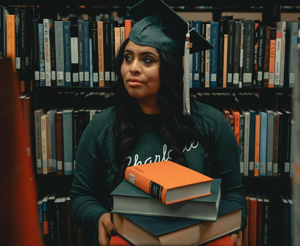 A graduate searching for books in the library.