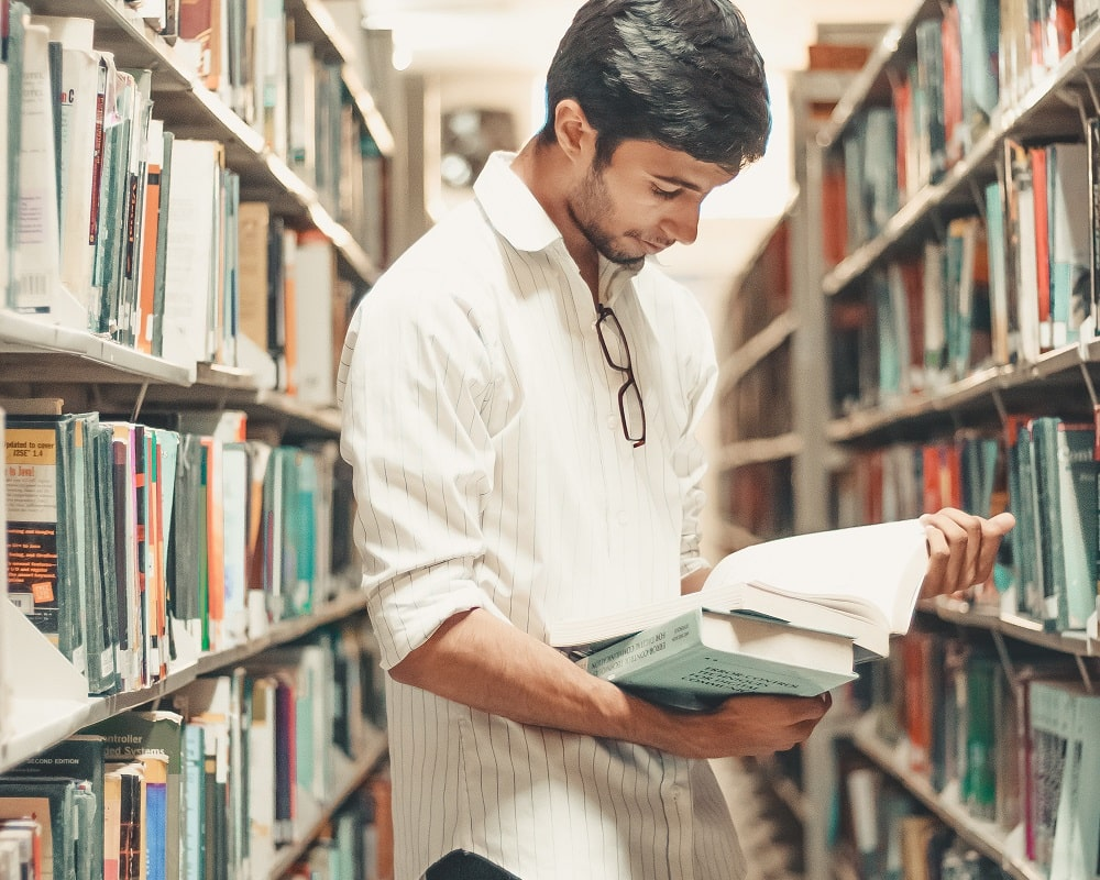 A close look at a college student searching through the books of the library.