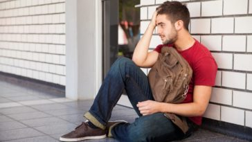A male college student sitting on the ground outside a campus building with his hand on his forehead, feeling low about failing a class.