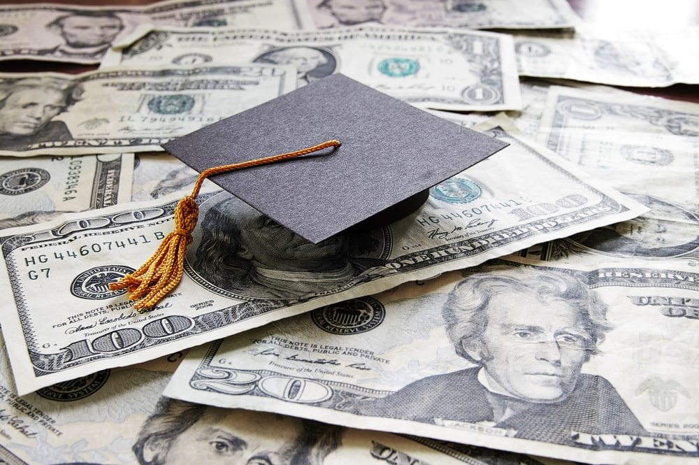 A graduation cap placed on top of a pile of dollar bills to signify a student's capacity to graduate resting on financial aid.