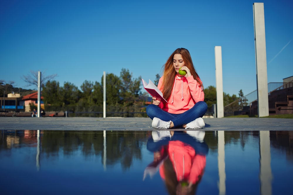 A female college student sitting by the water, reading a book and holding a fruit while reflecting on the way her college education is going.