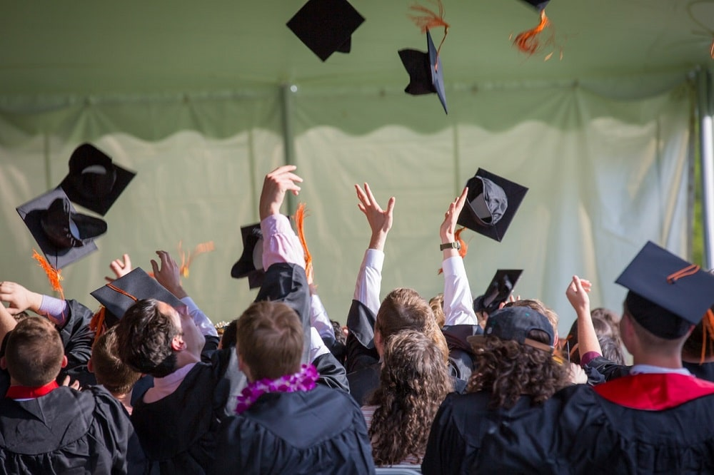 Students celebrating at a graduation ceremony, throwing their graduation caps in the air.