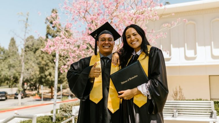 A couple of college graduates celebrate their victory by the school grounds.