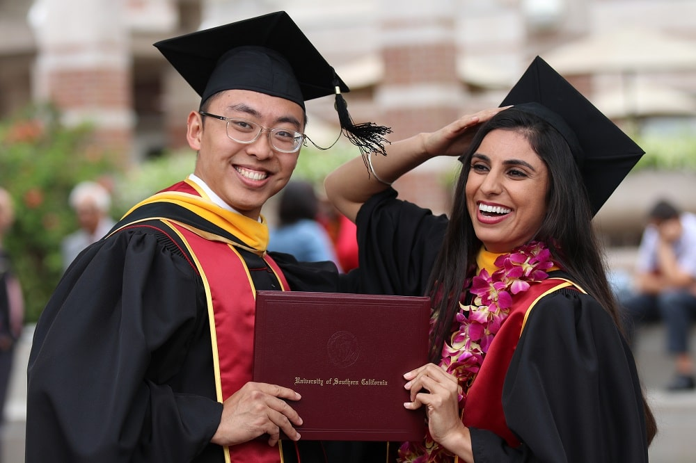 A couple of graduates celebrate with their hard-earned University diploma.