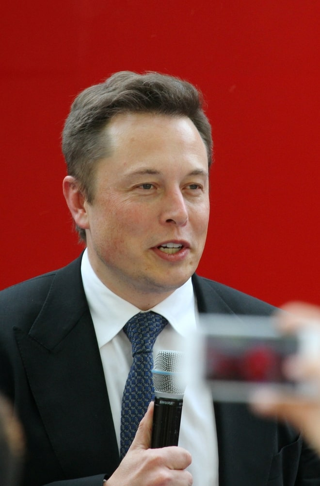 Elon Musk, CEO of Tesla, holding a microphone and giving a compelling speech.