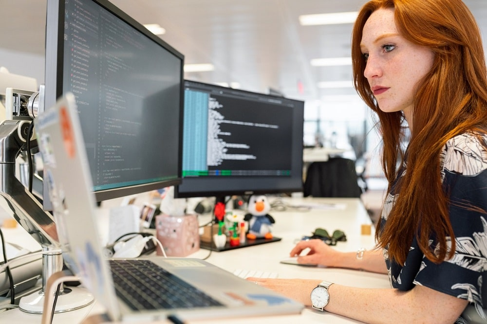 A computer science college graduate coding on a computer for her internship.