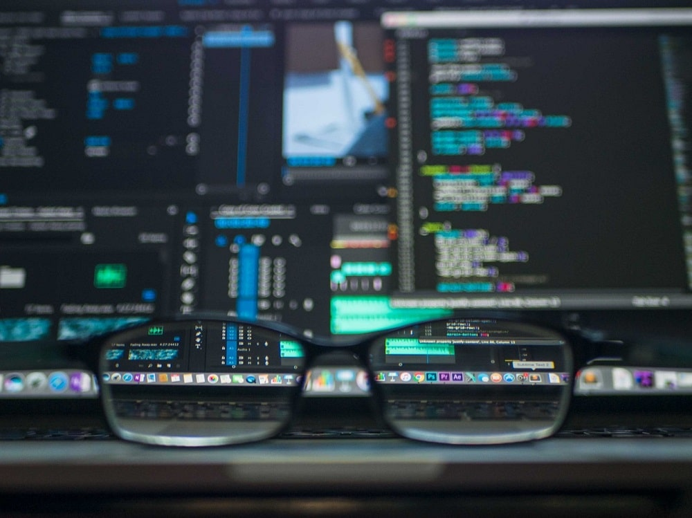 A back-end engineering intern's eyeglasses in front of a display monitor showing codes for the company database and systems.