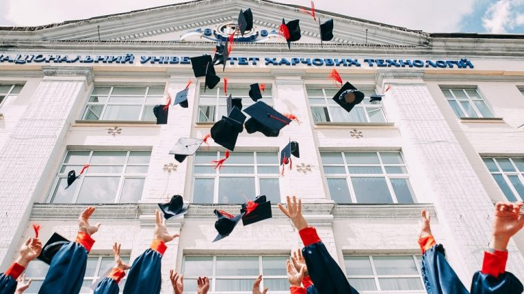 A batch of graduates tossing their graduation caps in the air.
