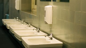 This is a close look at the communal bathroom row of sinks topped with mirrors.