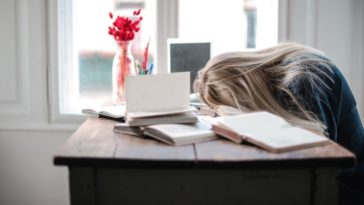 A student fell asleep studying on her desk.