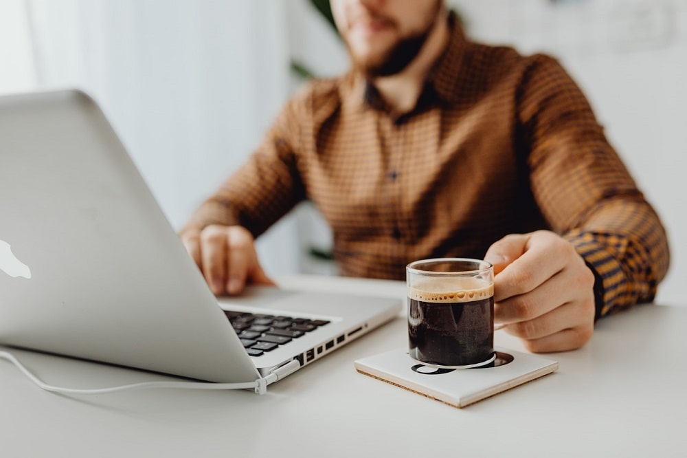 A philosophy major now working in the field of marketing, typing on his laptop and holding a cup of coffee on top of a coaster.