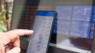 A close look at someone monitoring the trade and stock numbers in forex trading.