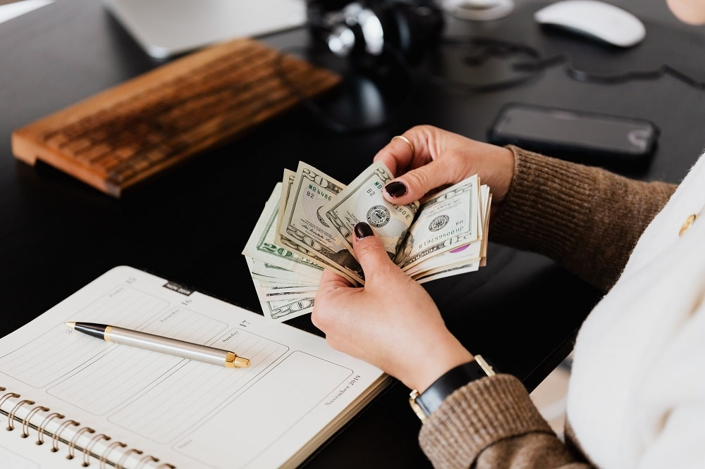 An accountant in the act of counting money in paper bills.