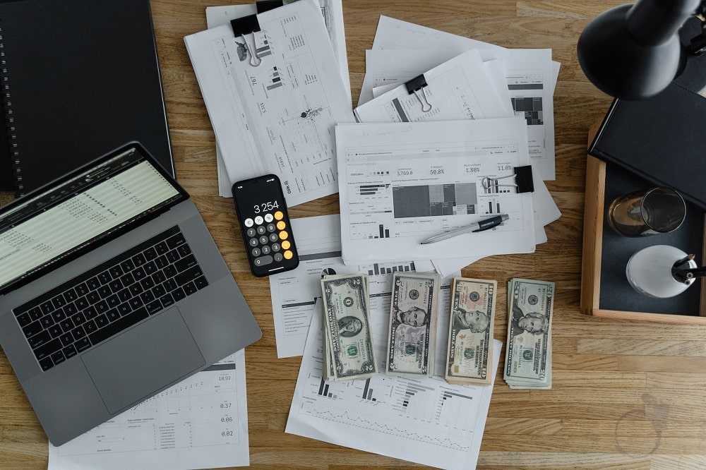 This is a close look at the desk of a finance officer with stacks of money and computations.