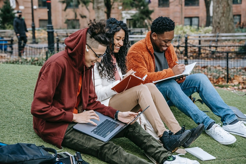 A group of students studying on the grass field.