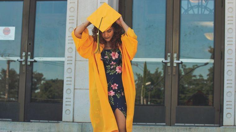 A graduate wearing a dark floral dress under her gown.