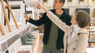 A mother helping his son pick out furniture for his dorm room.