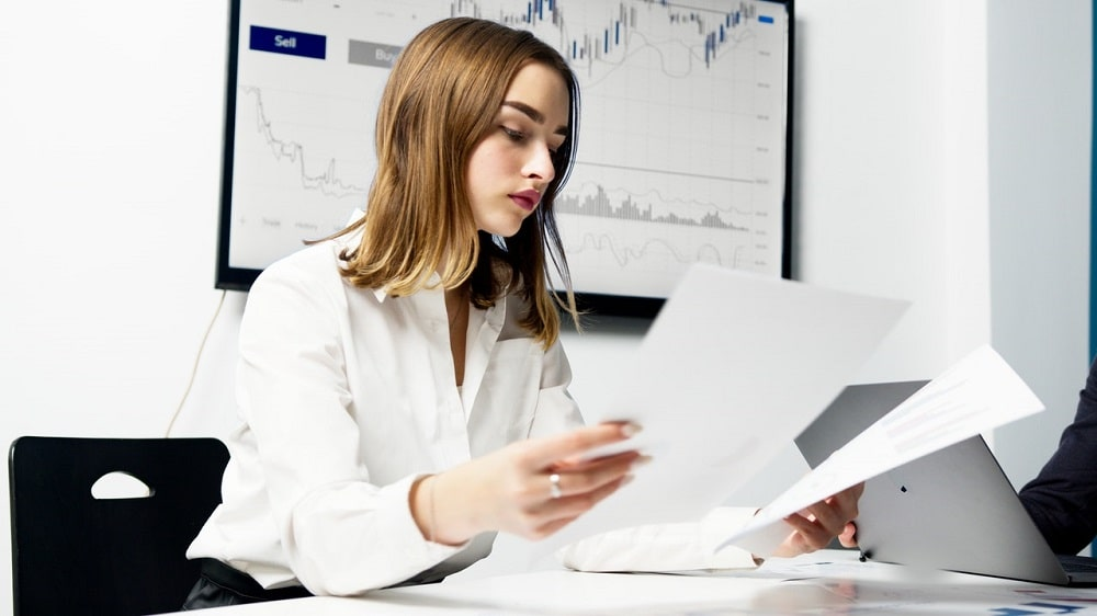 A finance major on her first job as a financial analyst, examining her reports at work.