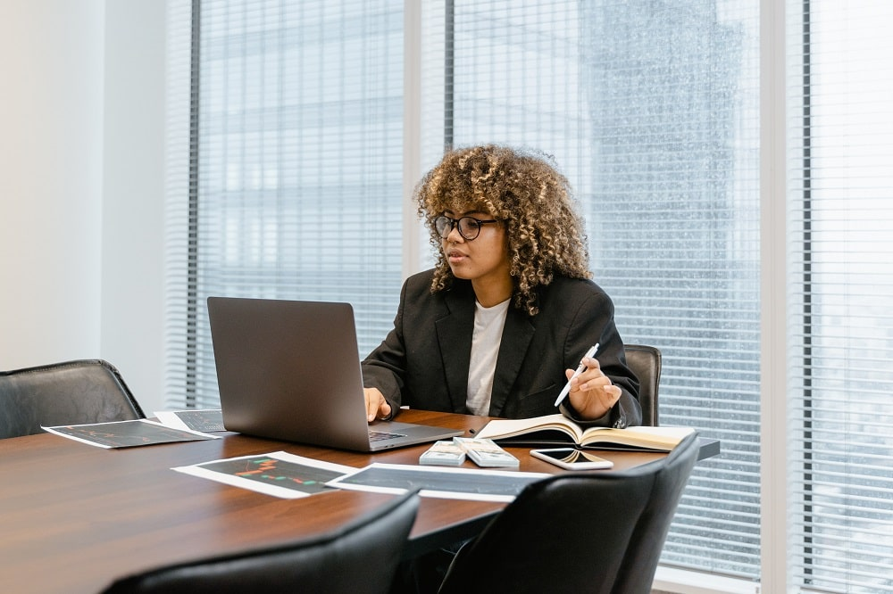 A finance graduate sitting at the conference table and in front of her laptop, hard at work on her job as a financial analyst.