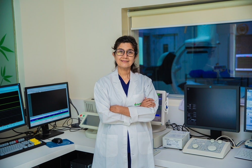 A doctor working in a laboratory with machines and computers.
