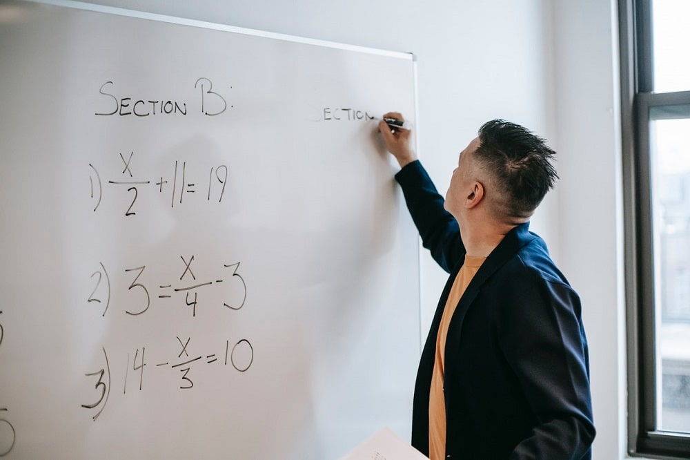 A mathematics teacher writing equations on the white board with a black marker, teaching basic algebra.