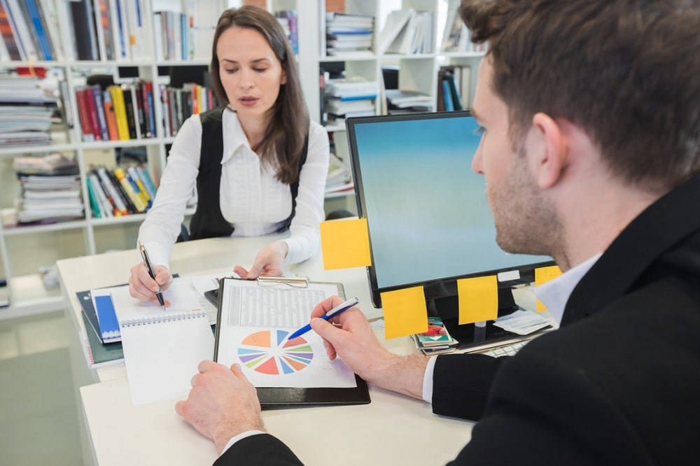 A statistician explaining the current trends to a client and pointing to the data on a printed material.