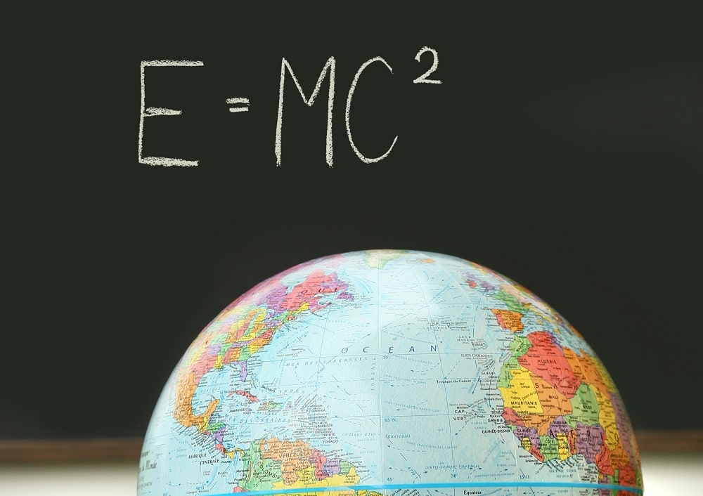 A close look at a globe and a blackboard showing the famous Physics equation of Einstein.