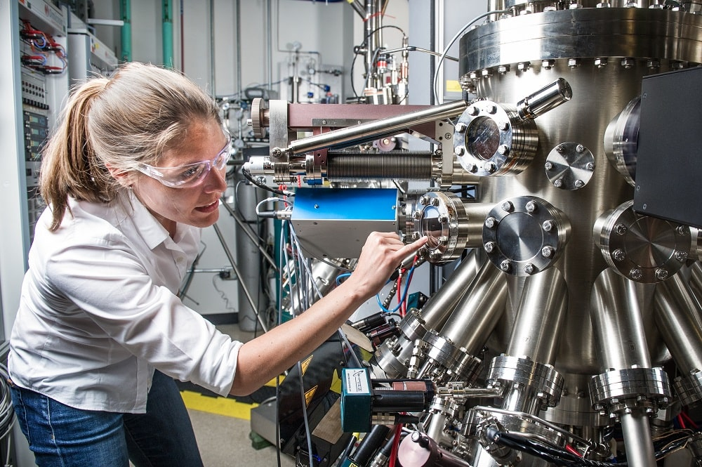 A research scientist inspecting the machinery in her laboratory.
